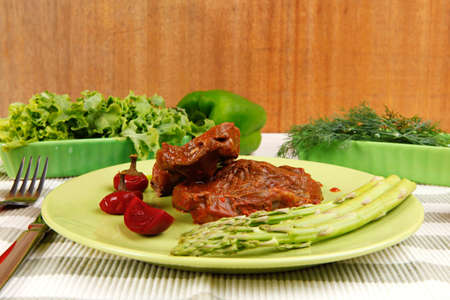 roast stew beef pork meat served with vegetables on green plate and cutlery on napkin over wooden table with red hot peppers photo