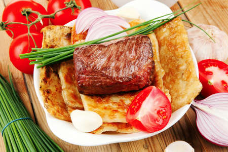 protein food: meat : grilled beef fillet mignon on bread with tomatoes salad on wooden table Stock Photo