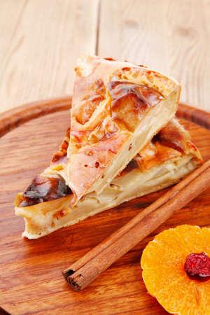 custard slices: sweet apple cake with lemon and cinnamon sticks on wooden table
