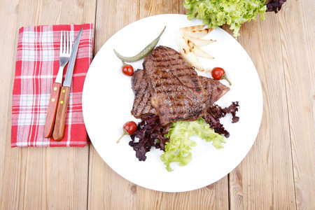meat food : two grilled steak on green lettuce salad , with roast onion and red hot chili peppers , on dish over wooden table Stock Photo