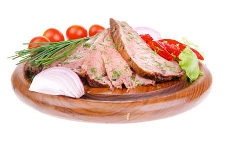 beef slices on plate with vegetables over wooden plate photo