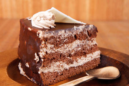 sweet brownie chocolate cream cake topped with white chocolate and cream with chocolate with chocolate sauce on wooden background photo