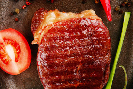 entree: meat entree : grilled beef steak served with hot cayenne peppers red tomato green chives on metal pan isolated over white background