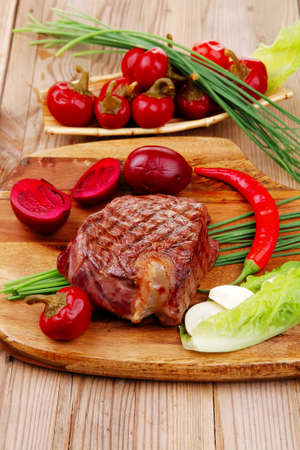 meat food : roast beef garnished with green staff and red chili hot pepper on wooden table with cutlery photo
