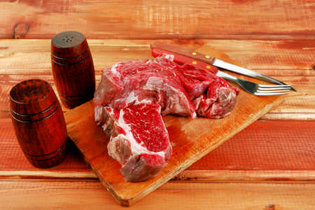 savory: red raw beef meat steak on wooden cutting board prepared for roasting photo