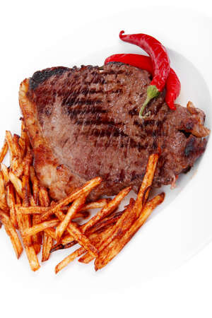 entree: entree : grill beef meat steak on white round plate with dry hot chili pepper and potato chips isolated on white background