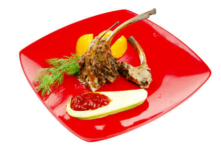 entree: main entree : grilled beff small ribs served with mango fruit and filled avocado on red dish isolated over white background