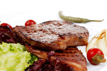 t bar: meat food : two roast steak boneless with red and chili peppers, served on green lettuce salad on dish isolated over white background Stock Photo