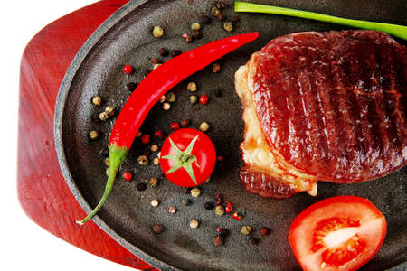 entree: main entree : platter of roasted beef steak served with hot cayenne peppers cherry tomato green chives on metal pan isolated over white background