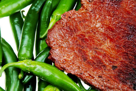 고기의: meaty food : roast meat steak on green hot chili peppers on a white background