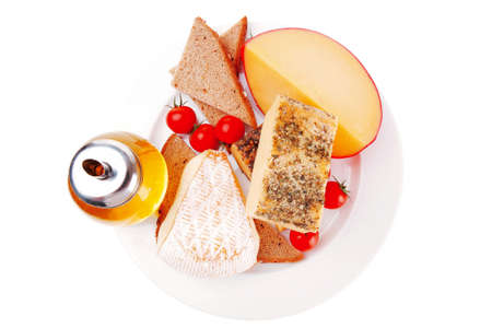 french aged cheeses on dish with bread and tomatoes photo