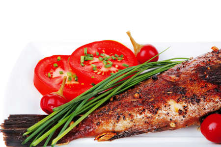 sunfish: savory isolated on white: whole fryed sunfish over plate with tomatoes lemons and peppers