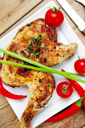 quarters: meat : chicken quarters garnished with red hot peppers on white plates over wooden table