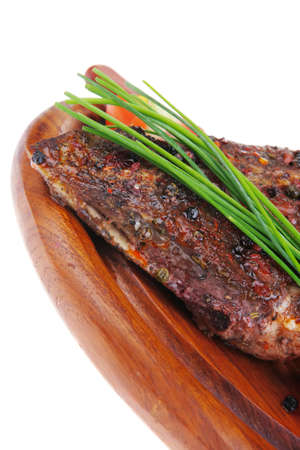 stell: meat savory on wooden plate: roast shoulder with tomato and chives isolated on white background Stock Photo