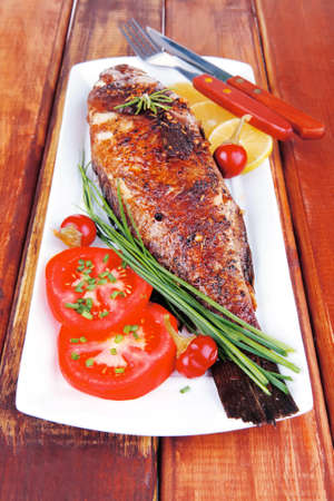 main course on wood: whole fryed sunfish on plate with lemons and peppers photo