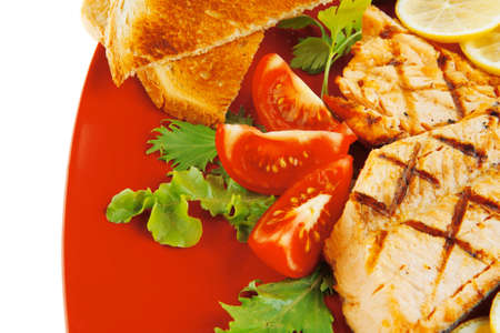 king salmon: grilled salmon steak on red plate with tomatoes