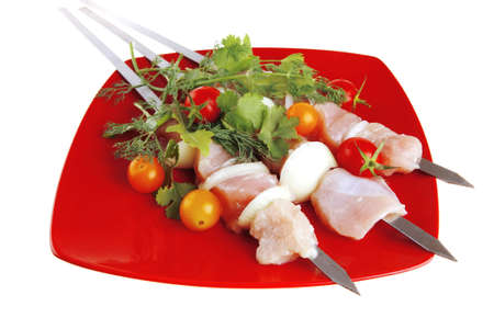 greenery: raw  chicken kebabs served with cherry and greenery Stock Photo
