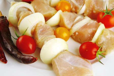 shish: raw chicken shish kebab on white plate