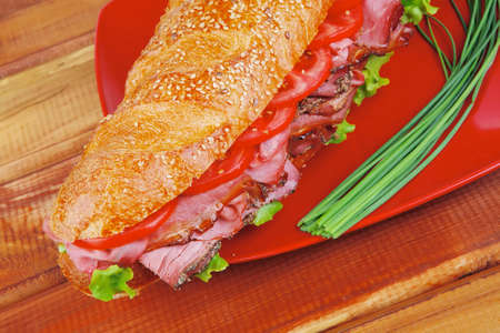 pepper castor: french sandwich on red plate : baguette with smoked sausage over wooden table