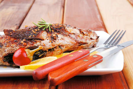 sunfish: main course on wood: whole fryed sunfish on plate with lemons and peppers