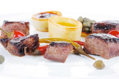 european food: alimentos Europea: roast beef estofado de carne en plato blanco sobre fondo blanco, con aj� picante, alcaparras y salsas