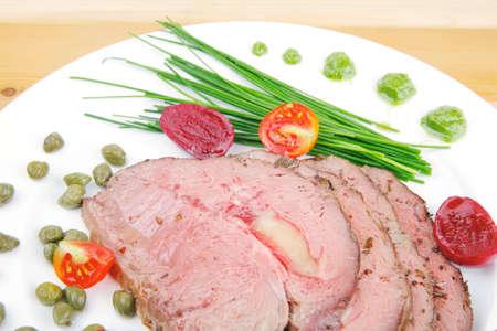 alcaparras: carne asada servida en un plato blanco con alcaparras sobre madera