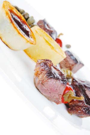 european food: Alimentaria Europea: roast beef goulash de carne sobre la placa blanca aislada sobre fondo blanco, con la pimienta caliente, alcaparras y salsas Foto de archivo