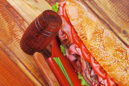 pepper castor: french sandwich on red plate : long baguette with smoked chicken sausage with sauces over wood