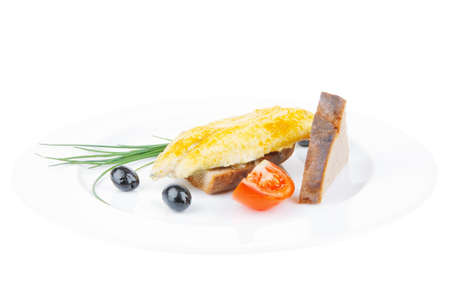 golden fish: main portion: served roast golden fish fillet over white plate with tomatoes and olives Stock Photo
