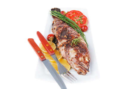 main course: served main course isolated on white: whole fried seabass on plate with lemons,tomatoes and peppers