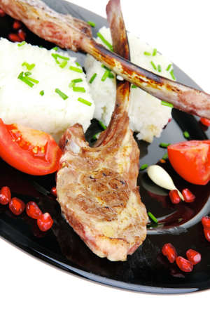 main course: main course: grilled ribs with rice and tomatoes on black dish over white background