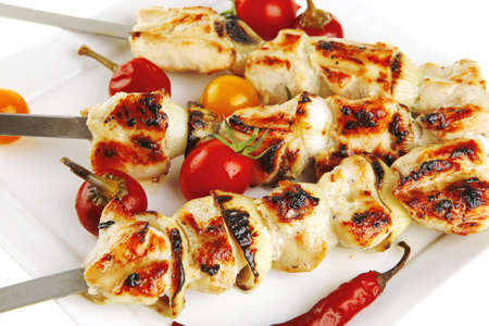 chicken shish kebab on white platter with vegetables Stock Photo