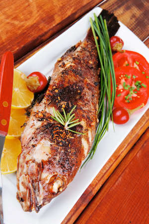 sunfish: whole fried sunfish over plate with tomatoes lemons and peppers Stock Photo