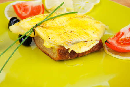 golden fish: served roast golden fish fillet over wooden table with tomatoes and olives
