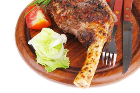meat over wood: grilled shoulder on plate with tomatoes green lettuce and cutlery isolated on white background photo