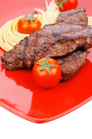 meat grilled: meat grilled beef steak with pasta and tomatoes on red plate isolated over white background Stock Photo