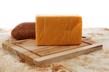 aged italian cheddar cheese on wooden board with rye ciabatta on used baking paper as background photo