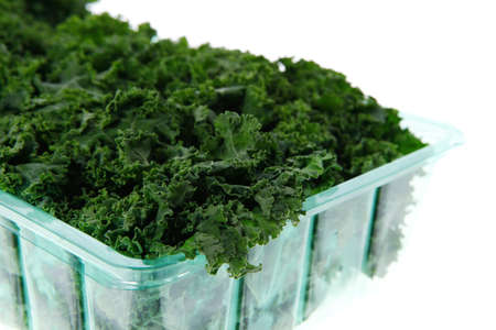 over packed: fresh raw green kale packed in plastic box ready to sell isolated over white background