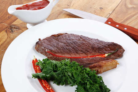 grilled beef steak fillet meat with red hot pepper and  raw kale leaf with ketchup sauce served on white plate over wood table photo