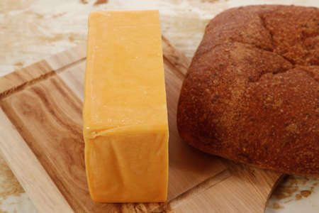 cheez: aged italian cheddar cheese on wooden board with rye ciabatta on used baking paper as background Stock Photo