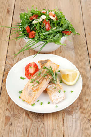 healthy fish cuisine  : grilled pink salmon steaks with vegetable salad on white dish over wooden table photo