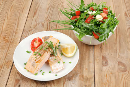 savory sea fish : baked salmon strips with vegetable salad on white dish over wooden table photo