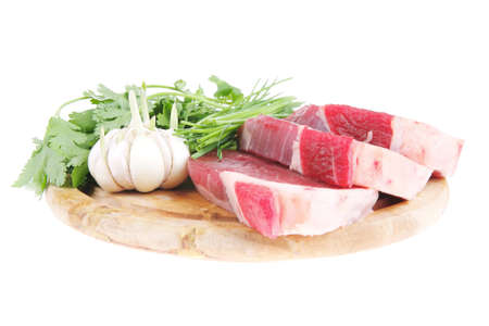 green stuff: fresh meat : raw uncooked fat lamb pork fillet with green stuff and garlic on wooden plate isolated over white background Stock Photo
