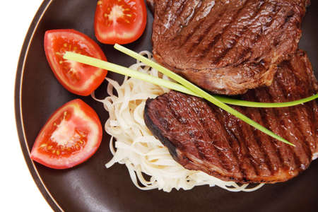 closeup of grilled steak with pasta and tomatoes on dark plate isolated over white background photo