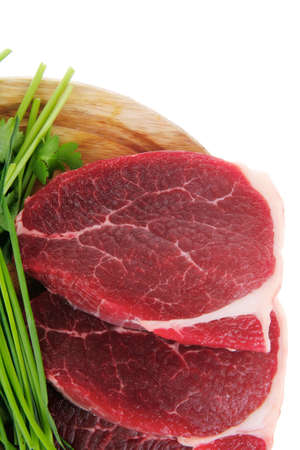 green stuff: raw meat : fresh beef pork fillet pieces with garlic and green stuff on wood isolated over white background