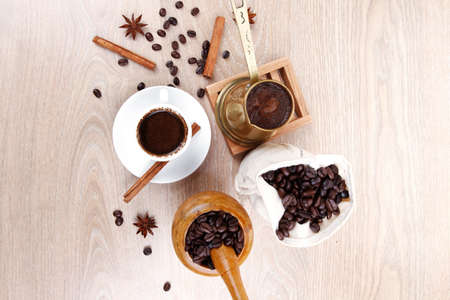 arabic coffee: sweet hot drink : black arabic coffee in small white cup with mortar and pestle , bag full beans, copper old style cezve , decorated with cinnamon sticks and anise stars Stock Photo