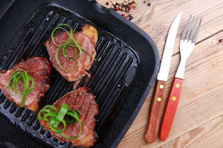 teflon: roast bloody beef fillet steaks on black teflon grill plate on wood