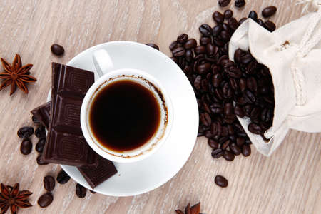 endorphines: sweet hot food: black coffee with dark chocolate and coffee beans in bag on wooden table Stock Photo