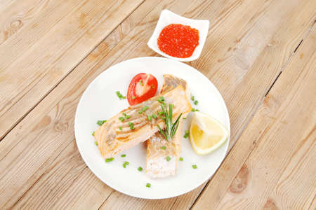 healthy fish cuisine  : grilled pink salmon steaks on white dish with red caviar over wooden table photo