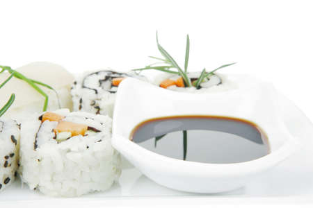 soysauce: Maki Rolls and California rolls made of fresh raw Salmon, Tuna and Eel with Cream Cheese and Avocado . Isolated over white background . on long white plate . Maki Sushi and Nigiri
